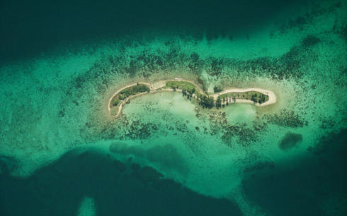 An aerial view of the vulnerable Laughing Bird Caye National Park island and coral reef in Belize from 6,000 ft.