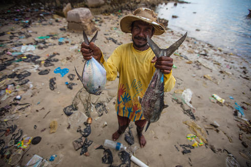 Man holding two fish on a trash filled beach
