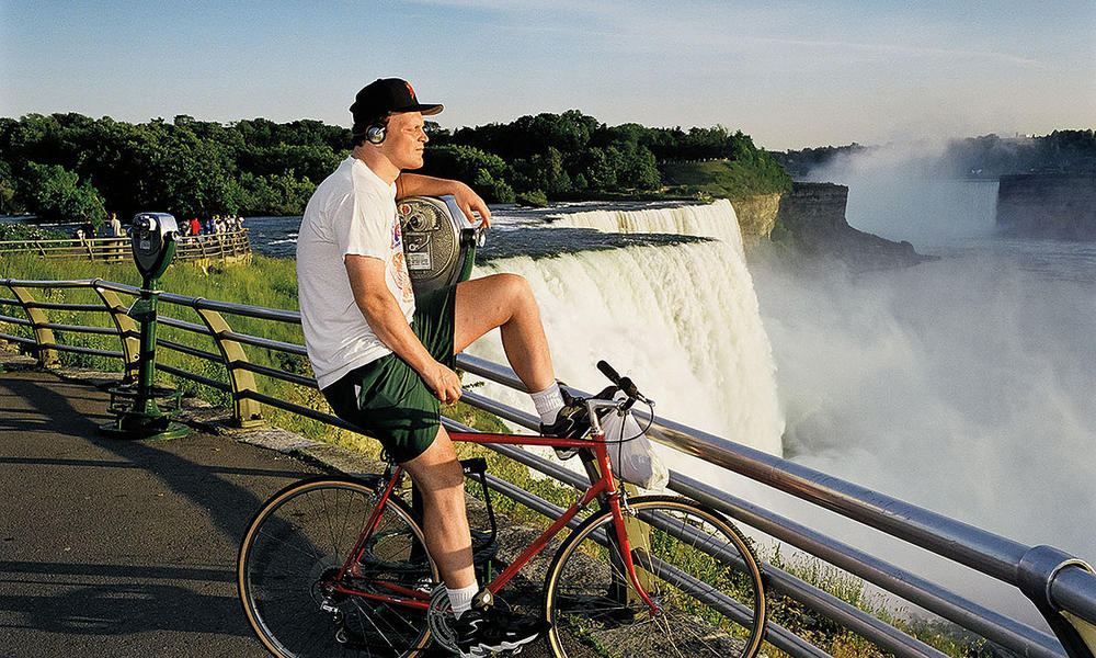 A man sits on his bicycle in front of waterfalls