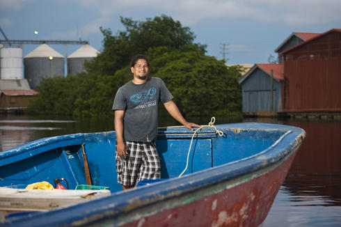 Belize City fisherman Levan Aldama stands in his boat