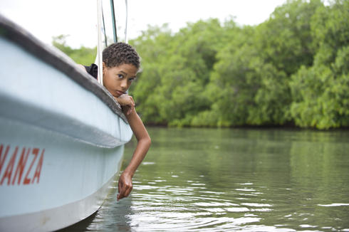 Emelly Miralda's son, Antonio, looks on as his mother fishes for bait in Placencia Lagoon