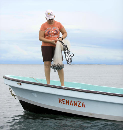 Emelly Miralda prepares to cast a net into the waters near her home