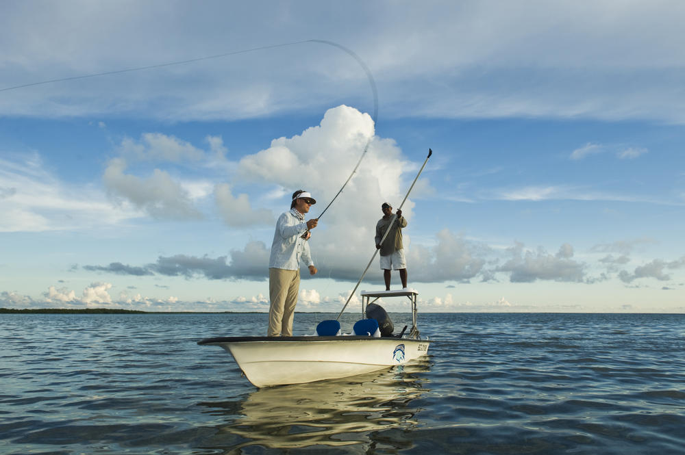 One person fishes while the other holds the boat in place with a long pole