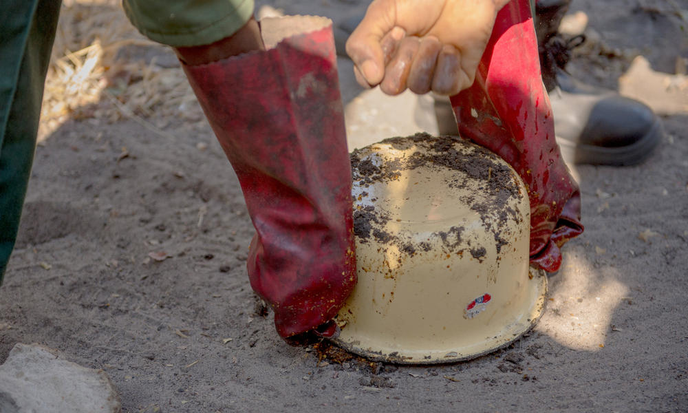Using a small pot, Mulanda molds the mixture into a cake.