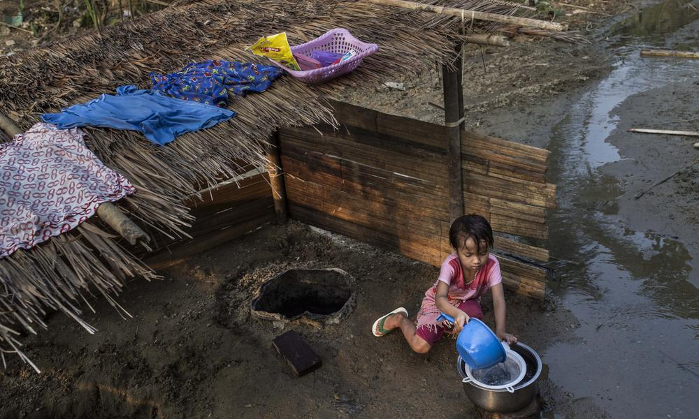 Little girl getting water from a well