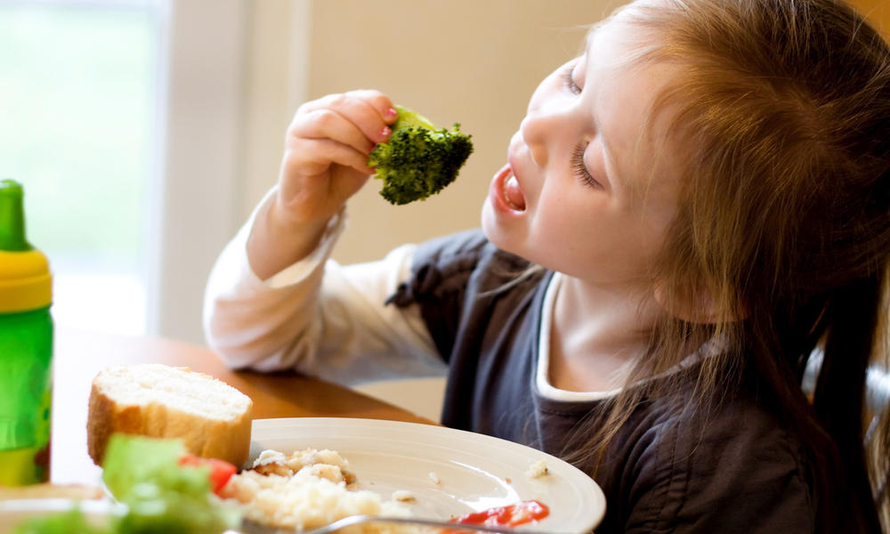 A young girl eating broccoli