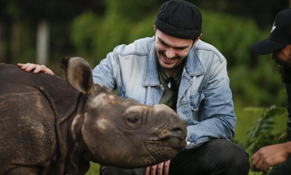 Nicholas Hoult with a baby rhino