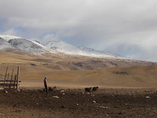 A landscape image with a man in the mountains of Kyrgyzstan