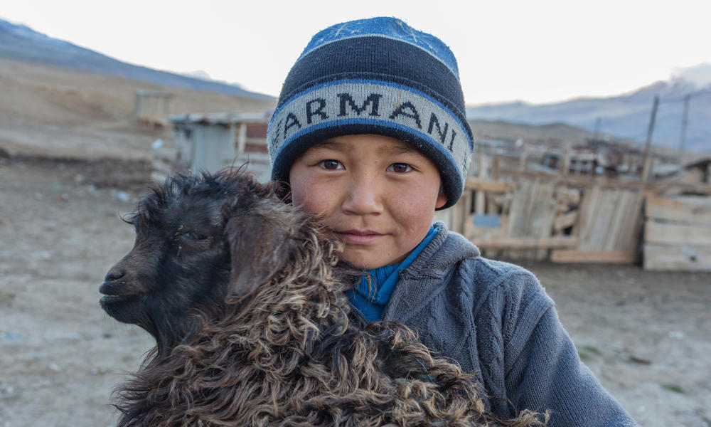 Child holding a goat in Ak-Shyrak, Kyrgyzstan