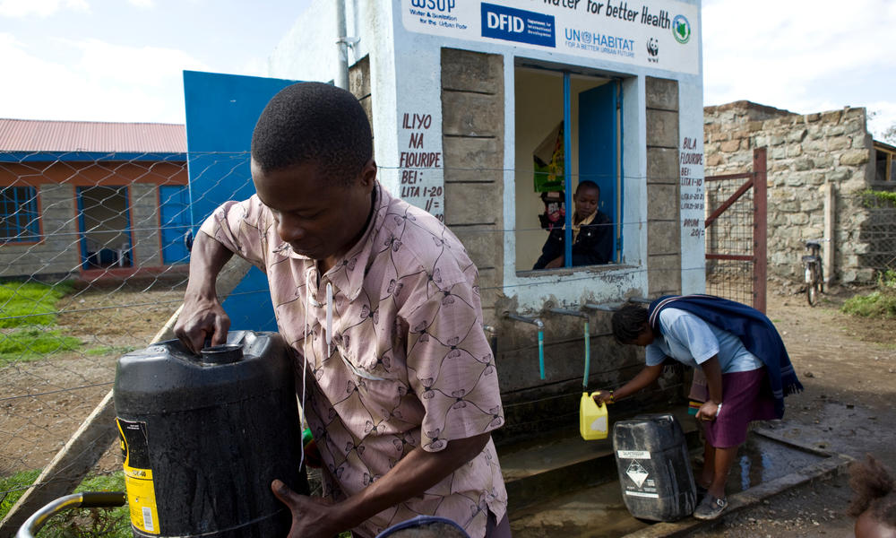 A young man collects water from a water kiosk in Kenya