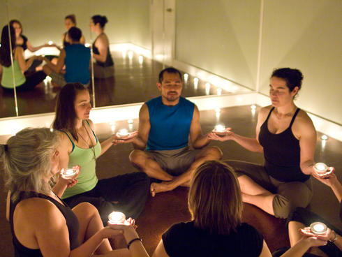A yoga group holding candles