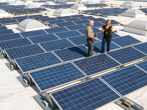 WWF's Marty Spitzer and Walmart's Katherine Neebe discuss sustainability issues on a Walmart roof, with solar panels.