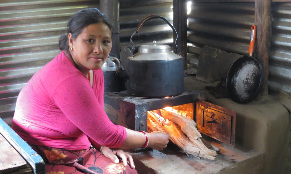 A woman cooking with a metallic improved cook stove.