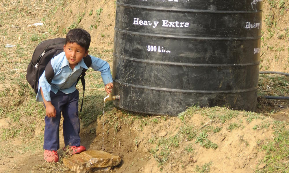 A child turning the faucet on a temporary water supply.
