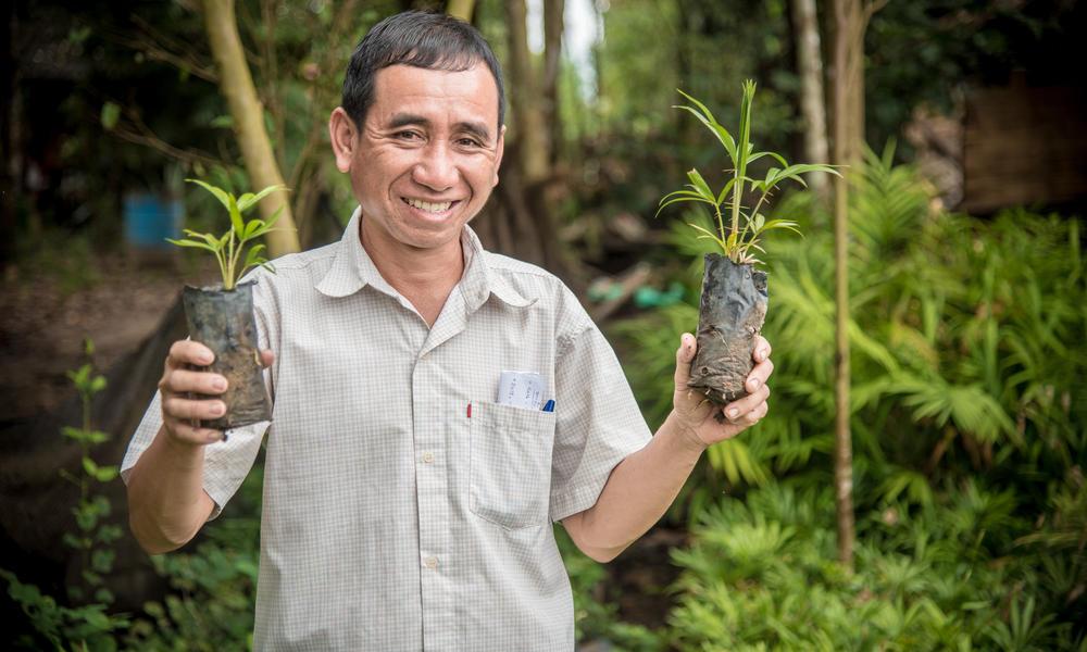 Khensy Milatid holding up rattan plants.