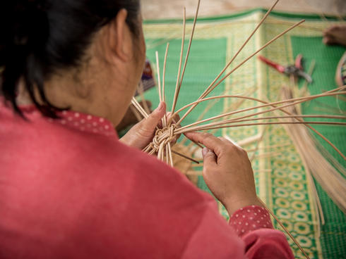 A woman basket weaving.