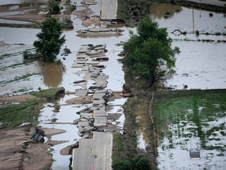 A road ripped apart by a flooding river.