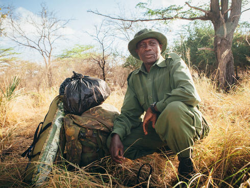 A wildlife ranger next to his kit bag and rations in Selous