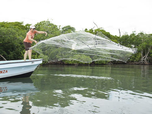 A woman throwing a fishing net in Belize.