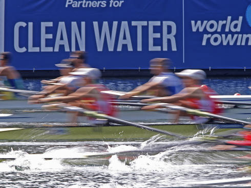Rowers and partners for clean water sign in the background.