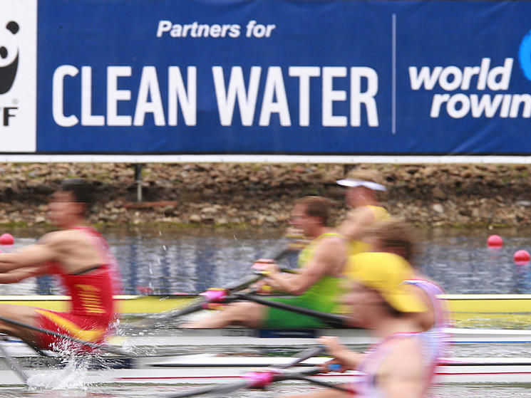 Blurred rowers with clean water sign in the background.