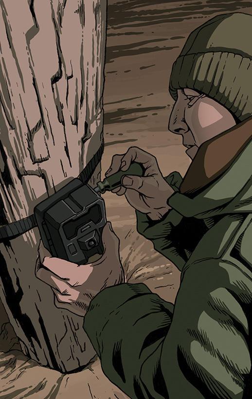 Researcher setting up a camera trap