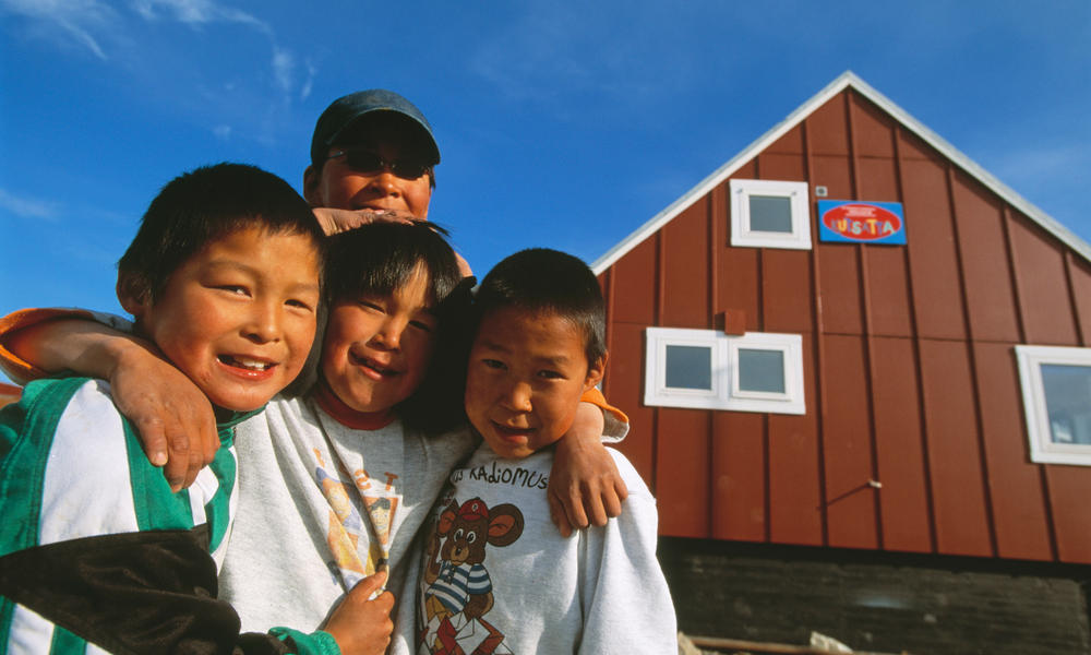 Inuit children smile in front of their home