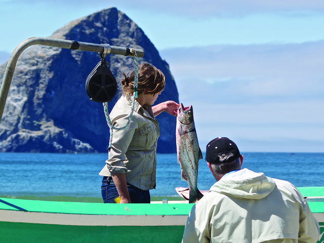 Oregon Department of Fish and Wildlife worker inspects a fish, Pacific City, OR