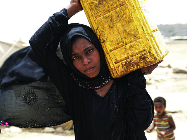 Achwaq, age 14, getting water at Khamir IDP Settlement, Khamir, Yemen