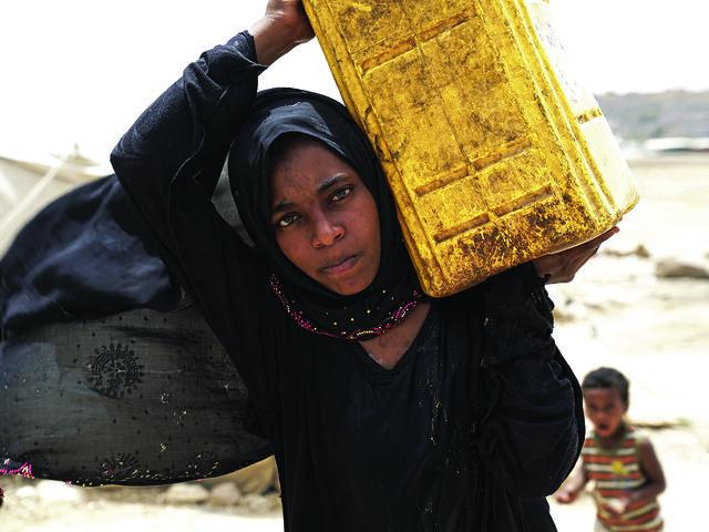 Achwaq, age 14, getting water at Khamir IDP Settlement, Khamir, Yemen