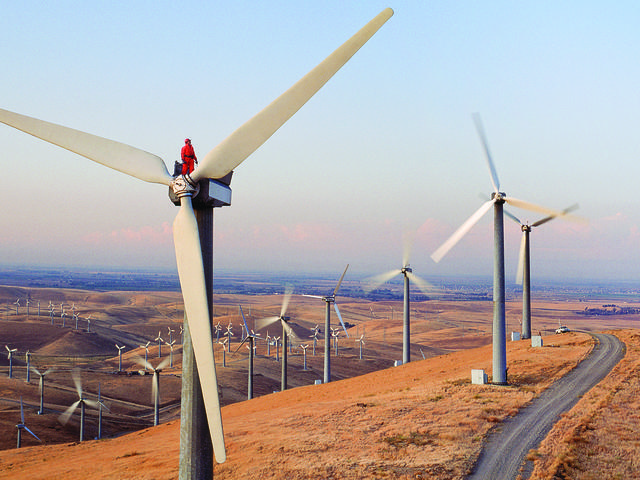 A worker inspects machinery atop a wind turbine