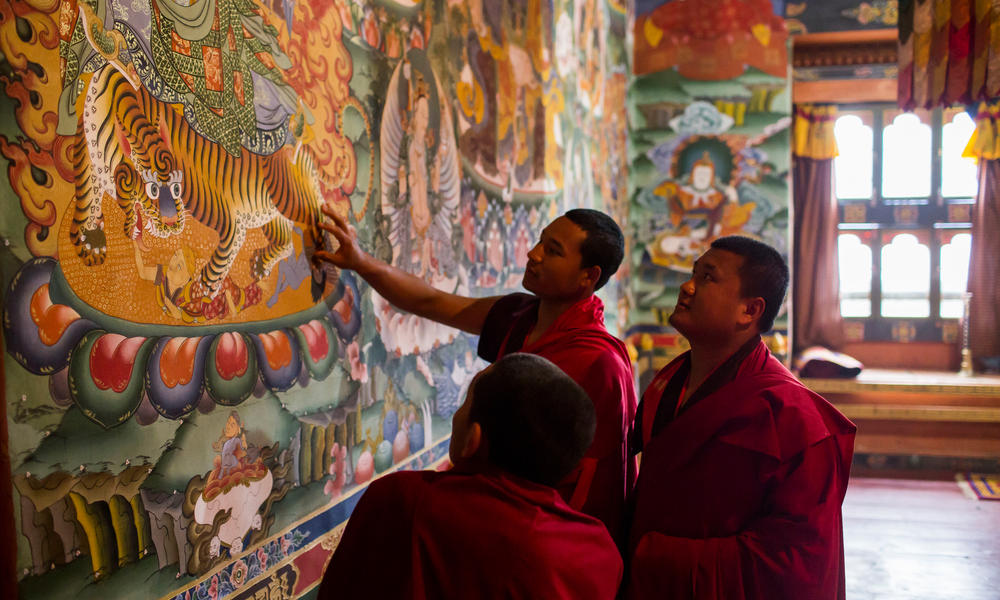Monks inspecting artwork