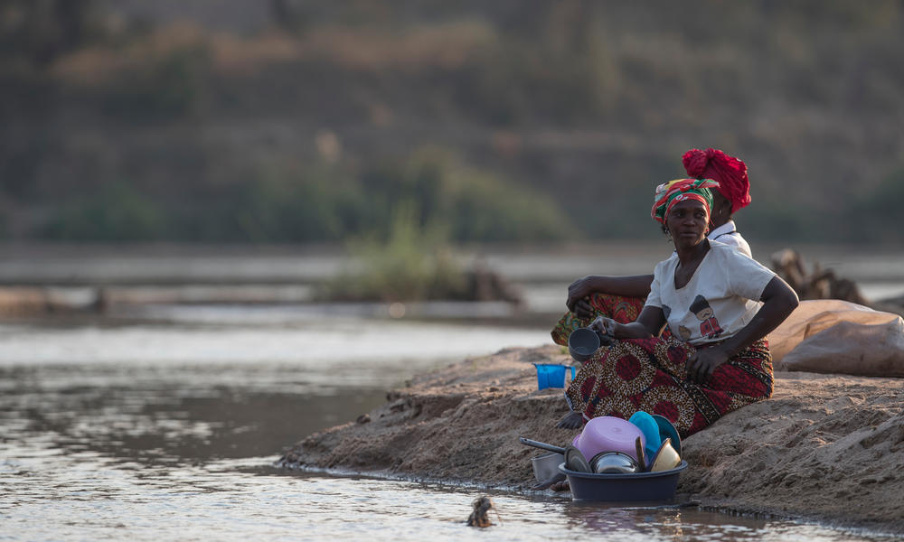 Two women use the river to wash up while avoiding the threat of crocodiles along the Luangwa River.