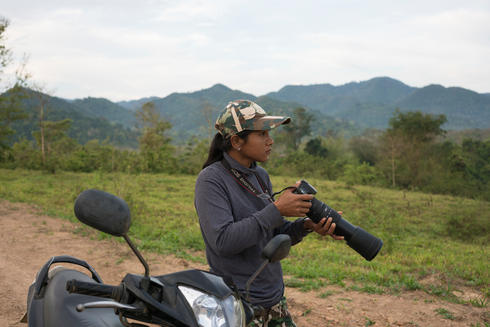 Woraya Makai (34) takes pictures of wild animals during an early morning patrol through the park. She's the only female ranger deployed in Kui Buri and in charge of photographing and surveying the animals she's seeing around the park.