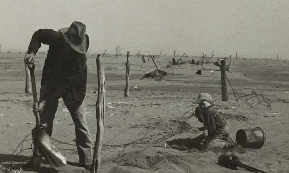 Dust bowl farmer raising fence to keep it from being buried under drifting sand
