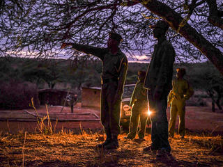 Conservancy rangers Musa, Daniel, Solomon and WWF-Kenya's Peter Loketeler on early morning patrol at Elangata Enderit village in lower Loita, Kenya.