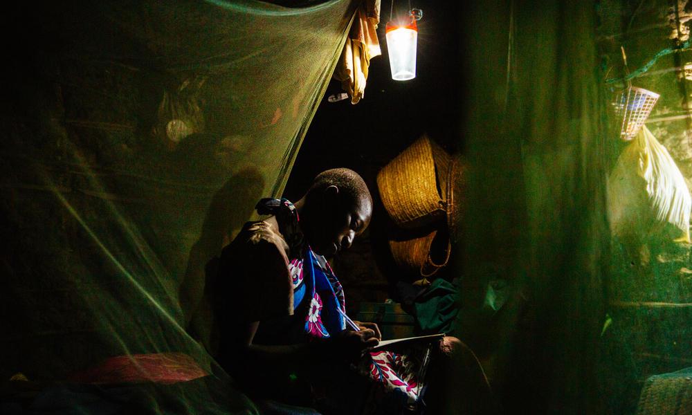 Dzame Shehi studies under a solar lamp