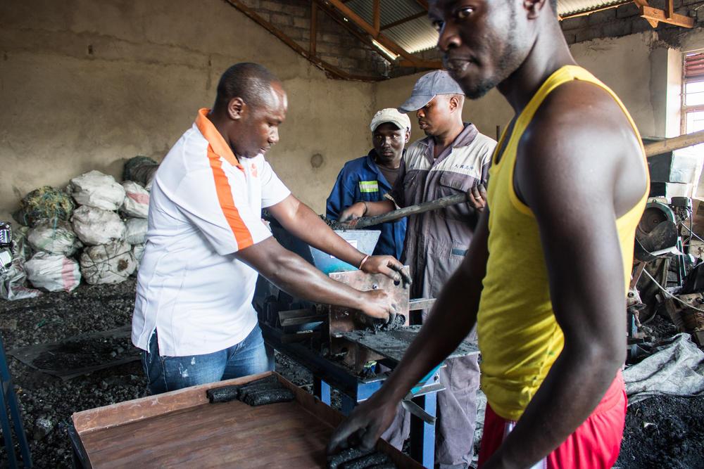 Men making stove briquettes