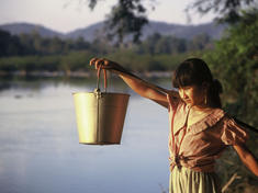Tribal girl collects water in the evening from the Serepok River