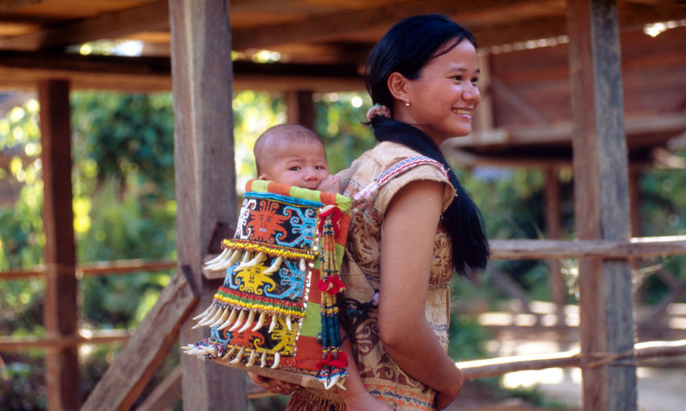 A Kenyah Dayak mother carrying her baby in a traditional hand made carrier