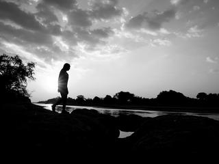 Agness Musutu, WWF's Young Expert Professional for the Freshwater Programme, walking along the edge of the Luangwa River at sunset in Mfuwe, Zambia