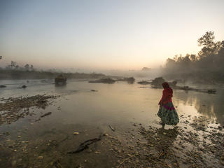 Woman walking through lake in Nepal