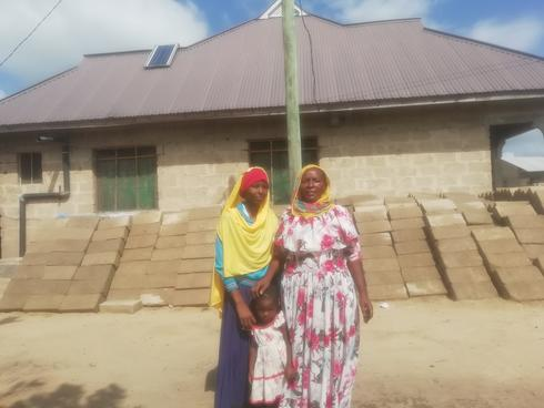 Sijali Kipuli with her daughter Alila and ground daughter Zulfak  in front of the latest house she has recently built  for 16,520USD