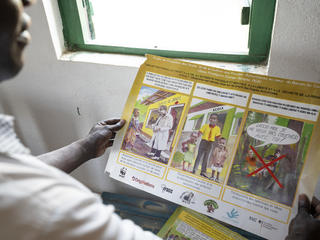 Yvon Amolet Martial, head lawyer at the Human Rights Center in Bayanga, Central African Republic, holding a poster targeted to BaAka people informing them of their rights.