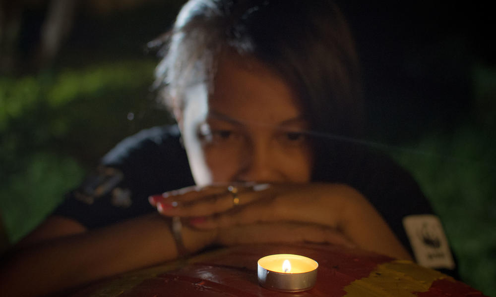 A woman reflects while looking at a candle