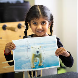 Child holding a picture of a polar bear