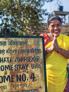 A woman greets with her palms together in front of a sign that advertises her villages homestay experience