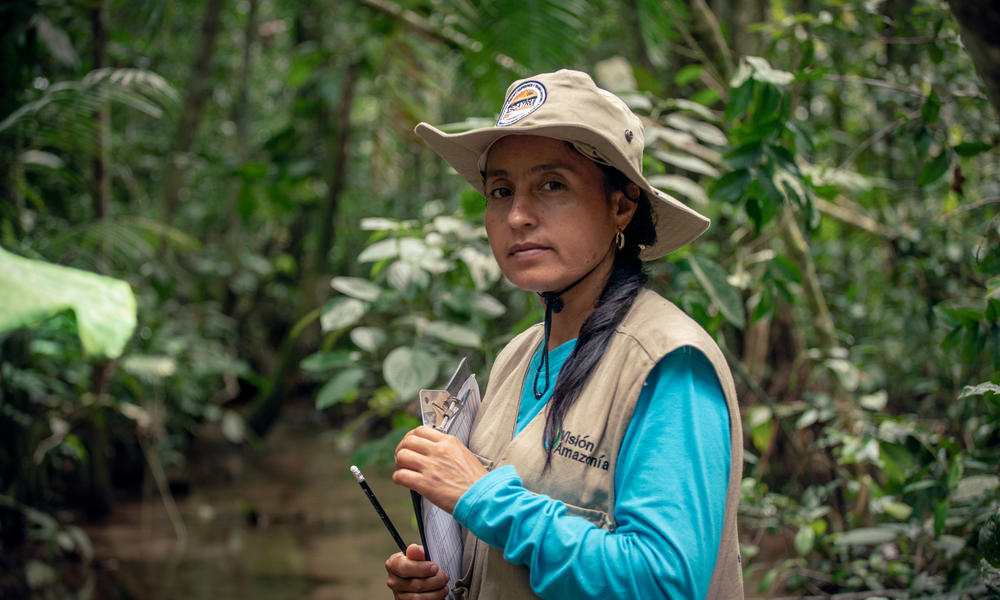 Portrait of Marisela Silva Parra standing in the forest with a clipboard