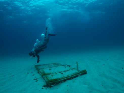 fisher dives to check on lobster trap in Bahamas