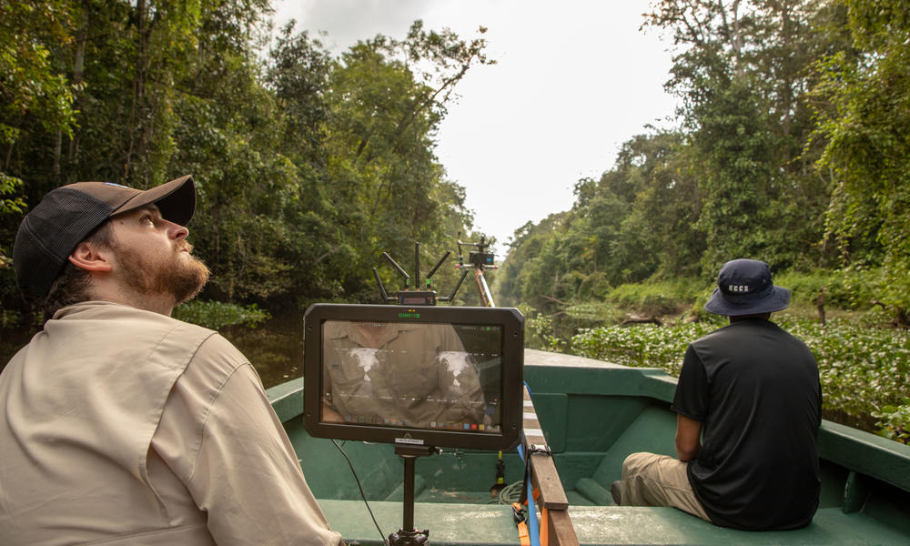 A behind-the-scenes photo of two team members in a boat going through the Bornean rainforest.